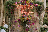 14 a whimsical and bold colorful twine wedding backdrop with vine circles, greenery, super bright blooms and a neon sign