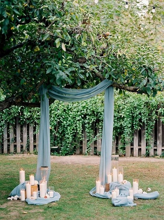 a creative backyard wedding arch made of a branch, blue fabric, candles all around is very eco-friendly as you are using a living tree