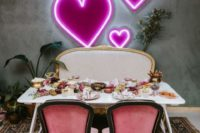 15 a wedding reception table with a pretty neon pink heart backdrop that creates a romantic ambience in the space
