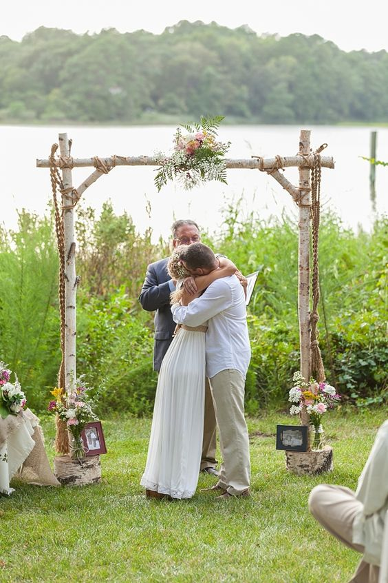 a rustic vintage wedding arch made of birchwood, with greenery and pink blooms, family photos