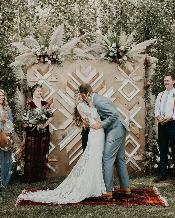 a boho backyard wedding backdrop of plywood, with geometric decorative patterns and some white florals and pampas grass on top