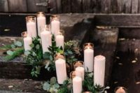 17 decorate your ceremony space with greenery and candles of various heights to make it more eye-catching