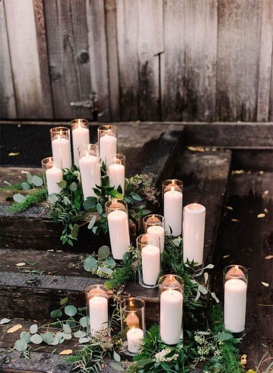 decorate your ceremony space with greenery and candles of various heights to make it more eye catching