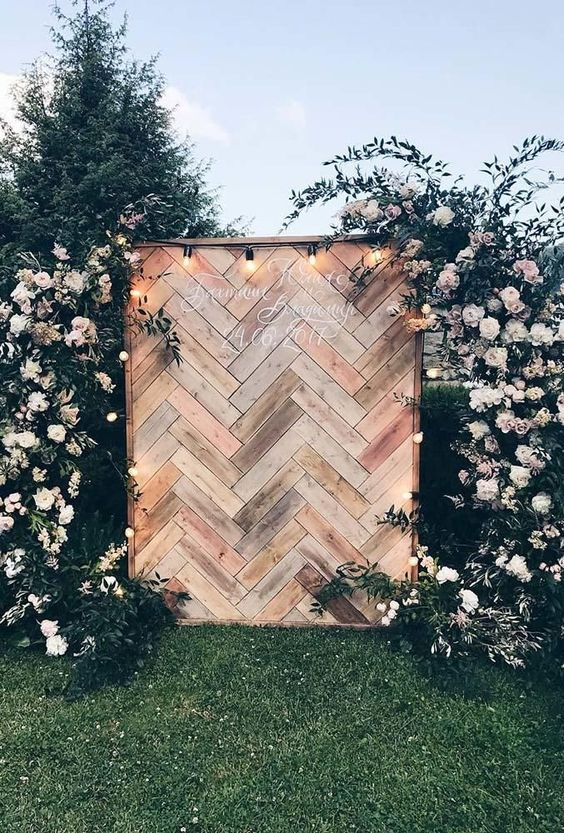 a boho backyard wedding backdrop of wood clad in herringbone patterns, with lush blush blooms and greenery around