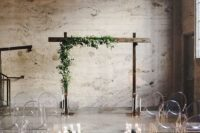 18 an industrial ceremony space with greenery, some blooms, candles, ghost chairs and a wedding arch with greenery