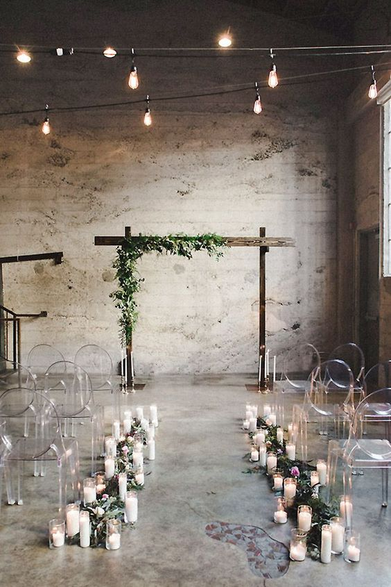 an industrial ceremony space with greenery, some blooms, candles, ghost chairs and a wedding arch with greenery