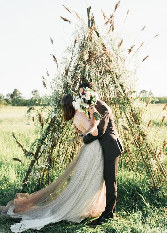a creative teepee wedding altar made of branches covered with greenery and some dried grasses for a fall boho wedding