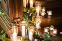 19 wedding reception decor with moss, pink petals and candles of various heights and sizes that look romantic