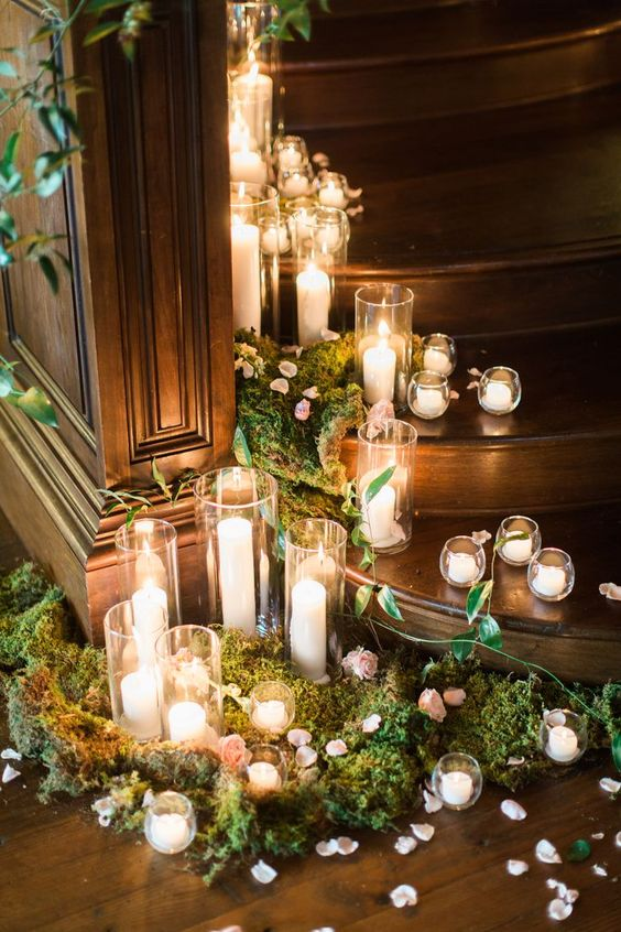 wedding reception decor with moss, pink petals and candles of various heights and sizes that look romantic