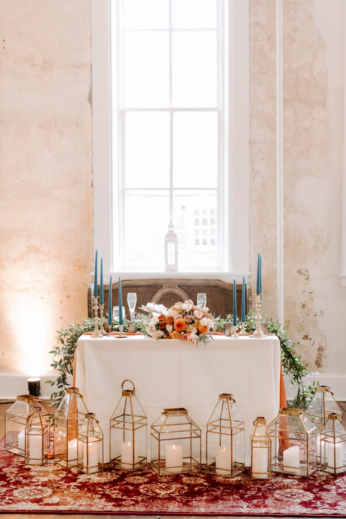 a colorful sweetheart table with greenery, blooms, blue candles and an arrangement of copper candle lanterns in front of the table