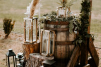 21 wedding ceremony space decor with candles lanterns of various sizes, candles, greenery and pampas grass