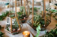 22 a pretty wedding centerpiece of geometric lanterns, greenery, succulents and thistles plus candles