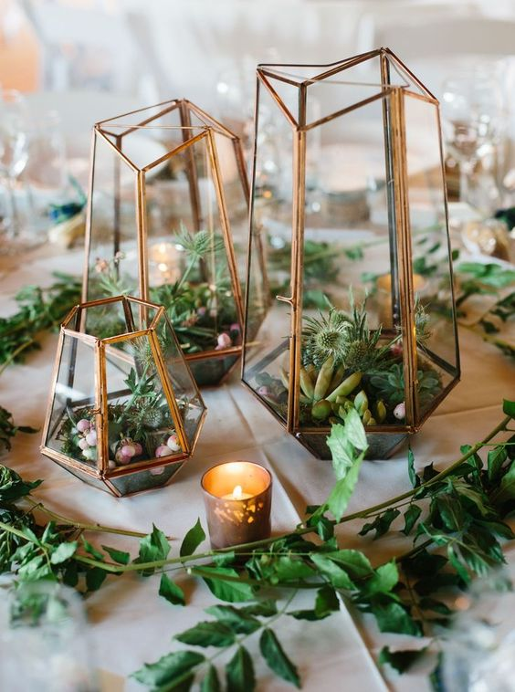 a pretty wedding centerpiece of geometric lanterns, greenery, succulents and thistles plus candles