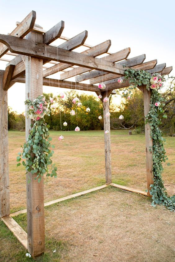 a rustic wedding chuppah with greenery, pink blooms and blooms hanging in bubbles over the space