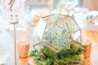 23 a chic wedding centerpiece of a wood slice, candles, moss, a terrarium with succulents and grasses on top