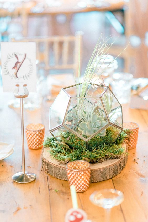 a chic wedding centerpiece of a wood slice, candles, moss, a terrarium with succulents and grasses on top