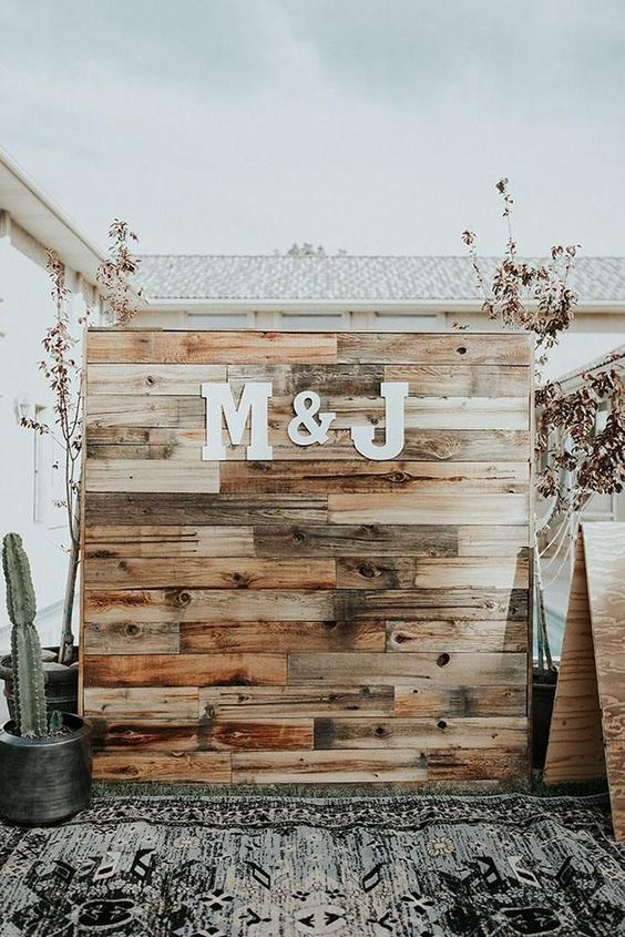 a simple rustic wedding backdrop of stained reclaimed wood, with monograms, a boho rug and a cactus next to it