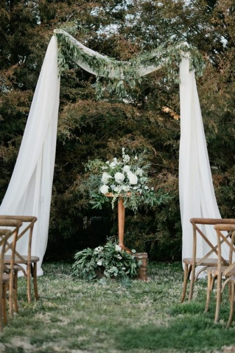 airy white fabric attached to the trees as an arch, with greenery and white blooms and a table with the same decor