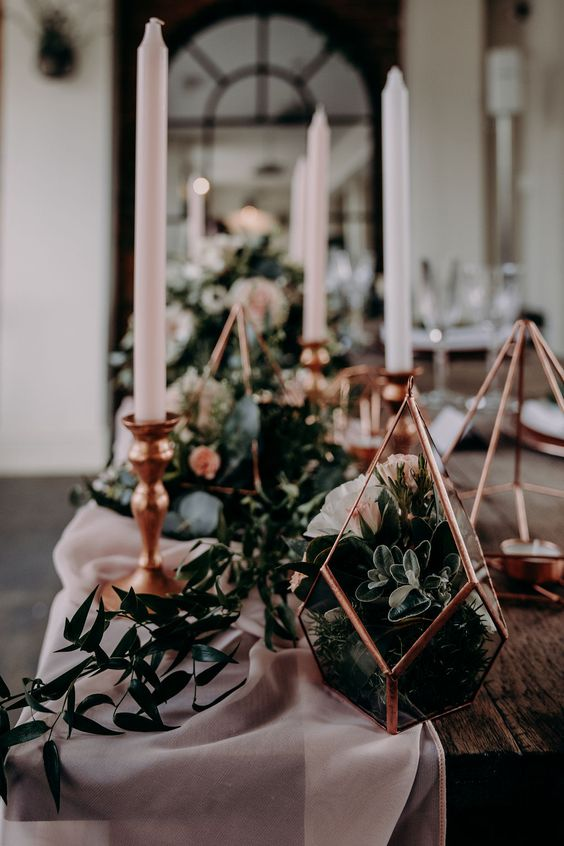 wedding decor done with greenery, blush candles and a blush runner, copper terrariums with greenery and succulents