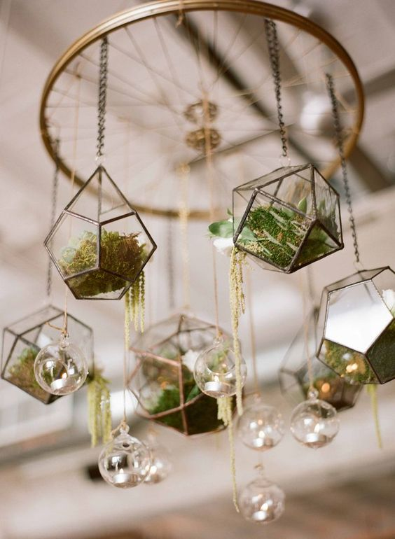 a wedding chandelier with hanging terrariums, with greenery, succulents and moss plus hanging candles