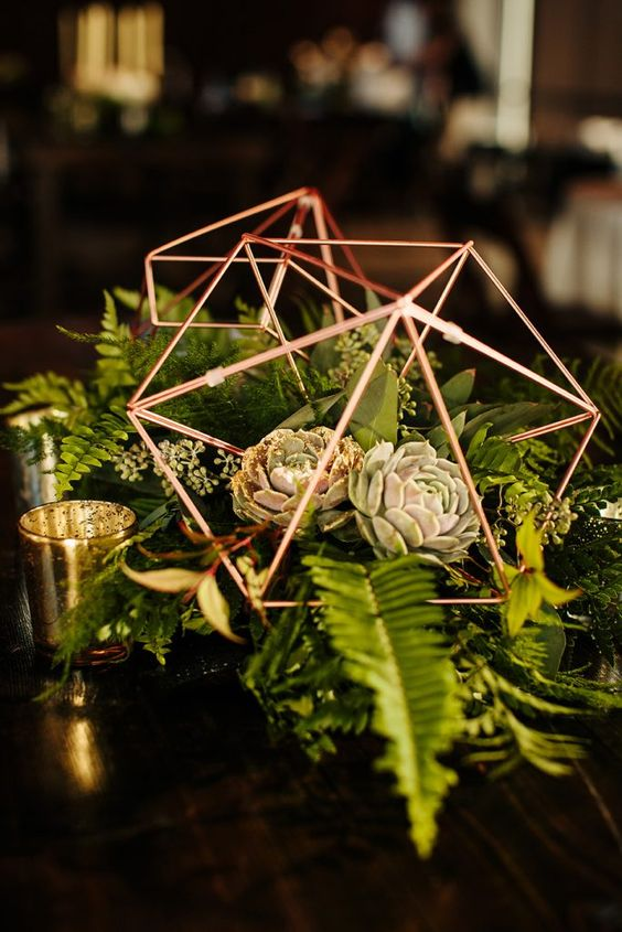 a pretty wedding centerpiece of copper terrariums with greenery and leaves plus succulents and gilded candle holders