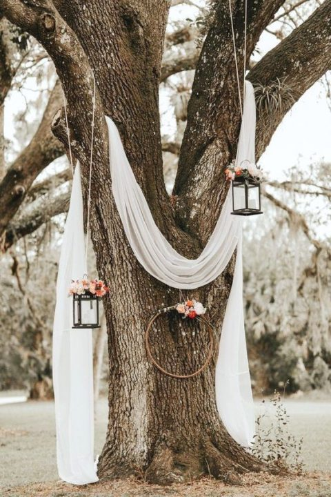 white airy fabric on a living tree, with candle lanterns decorated with bright blooms and a hoop