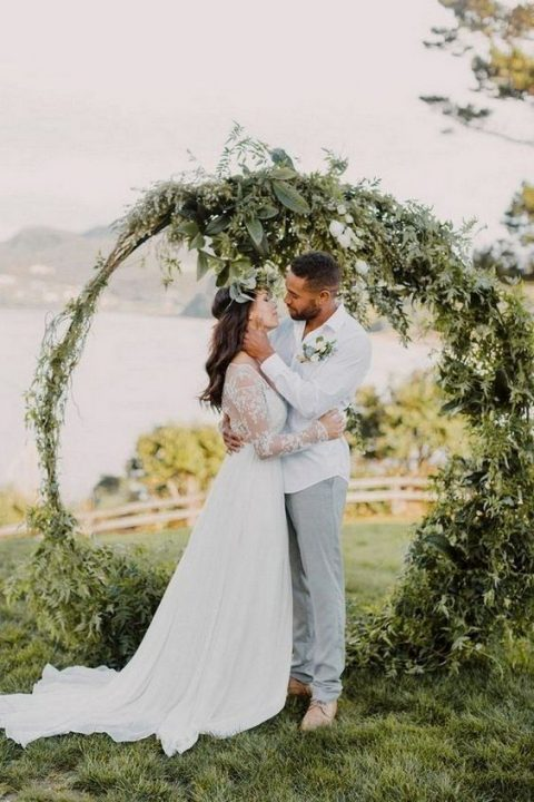 a large circular wedding arch covered with textural greenery instead of blooms will save your budget