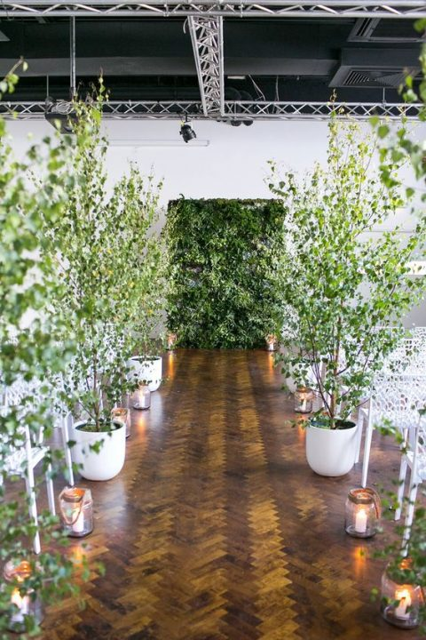 a living greenery wall and potted trees turn the indoor ceremony space into a real indoor forest