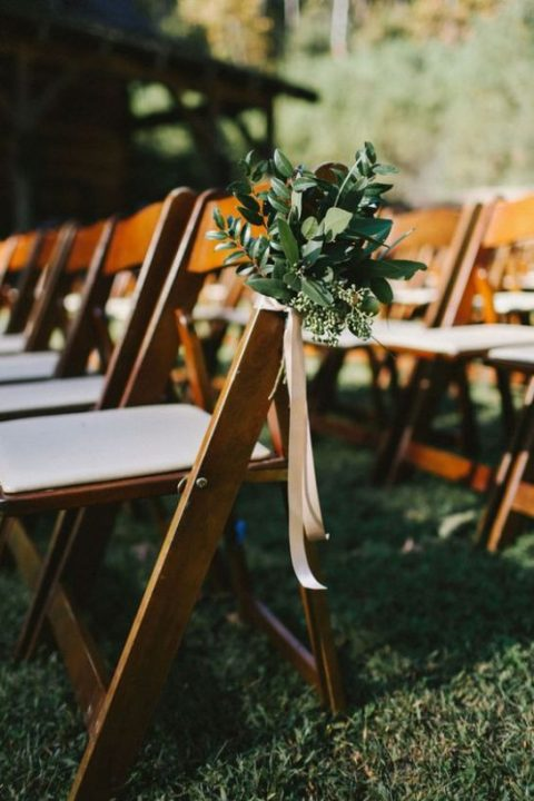 decorate your wedding aisle chairs with textural greenery and ribbons for a chic and simple look