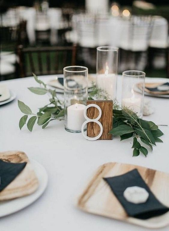 a casual backyard wedding centerpiece of greenery, pillar candles and a wooden table number is chic and stylish