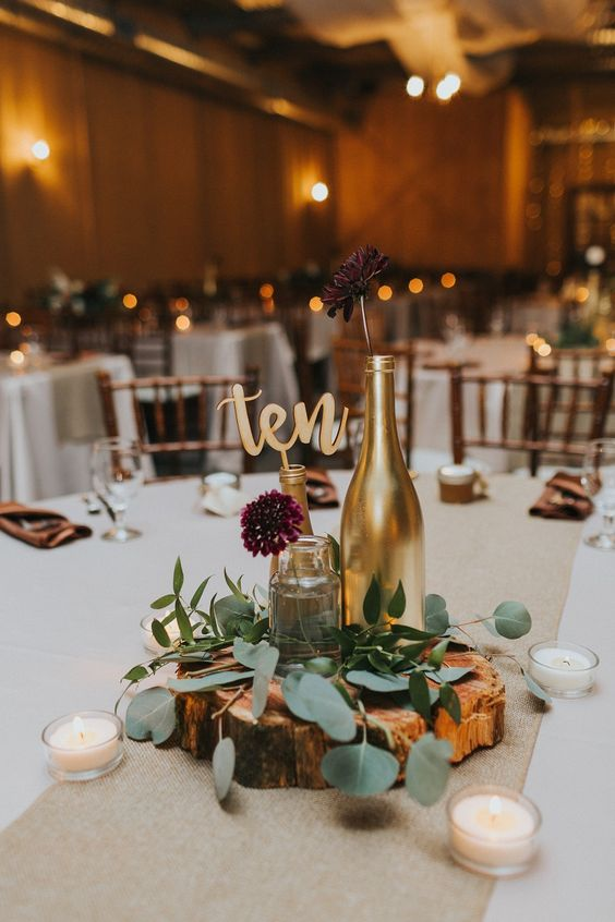a casual rustic wedding centerpiece of a wood slice, candles, greenery, gilded bottles and burgundy blooms for a backyard celebration