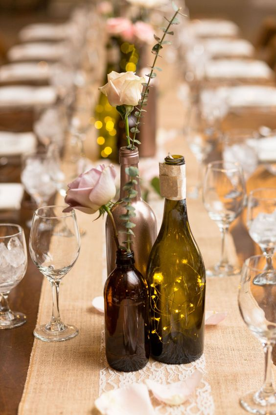a chic centerpiece of bottles with blush roses, eucalyptus and lights is a cool idea for a backyard wedding