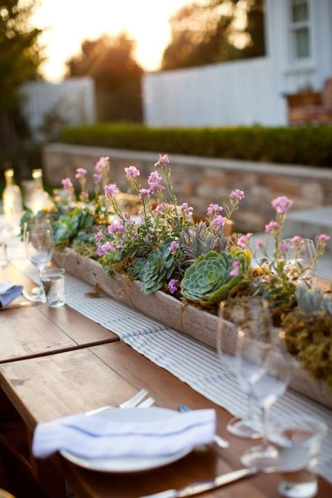 a long wooden planter with succulents and small pink blooms over a striped table runner is a cool backyard centerpiece idea
