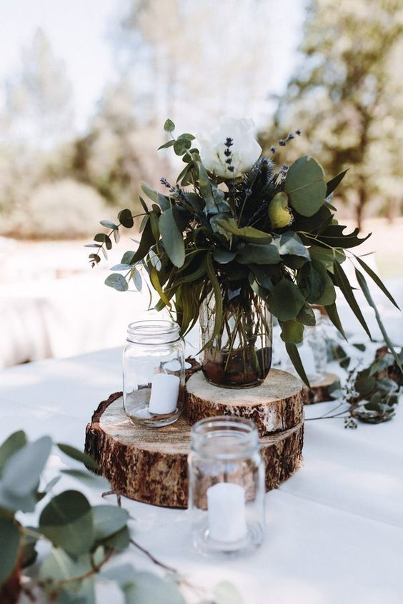 a rustic backyard wedding centerpiece of wood slices, candles, a greenery and lavender arrangement on top