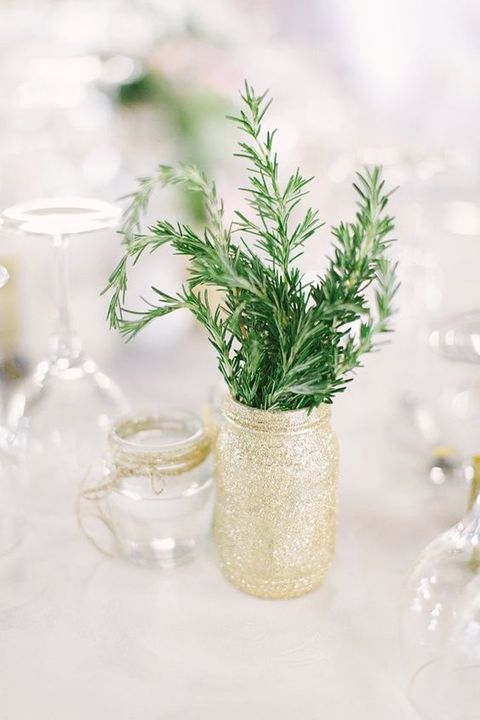 a simple backyard wedding centerpiece of a gold glitter jar and some greenery in it plus a jar with a floating candle