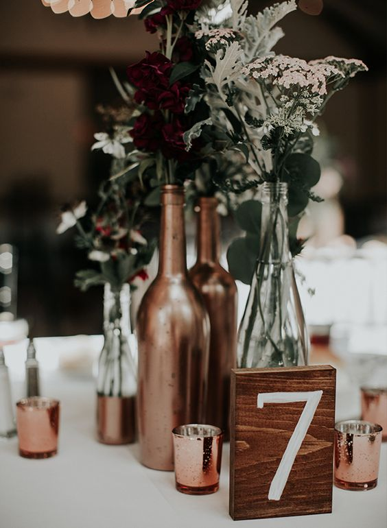 a simple backyard wedding centerpiece of sheer and gilded bottles, gold candle holders and wildflowers and greenery