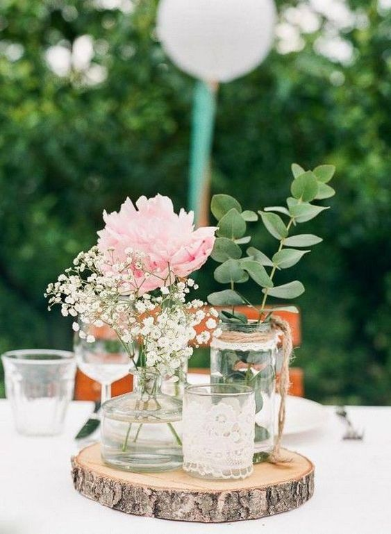 a simple rustic wedding centerpiece of a wood slice, a candleholder in lace, jars and bottles with greenery, a peony and baby's breath