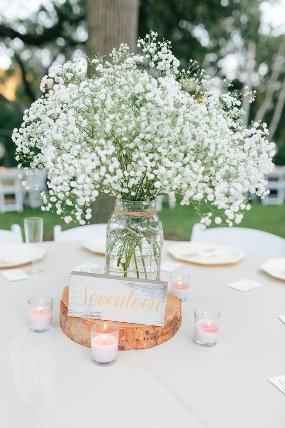 a simple wedding centerpiece of a wood slice, a jar with baby's breath, a table number and candles