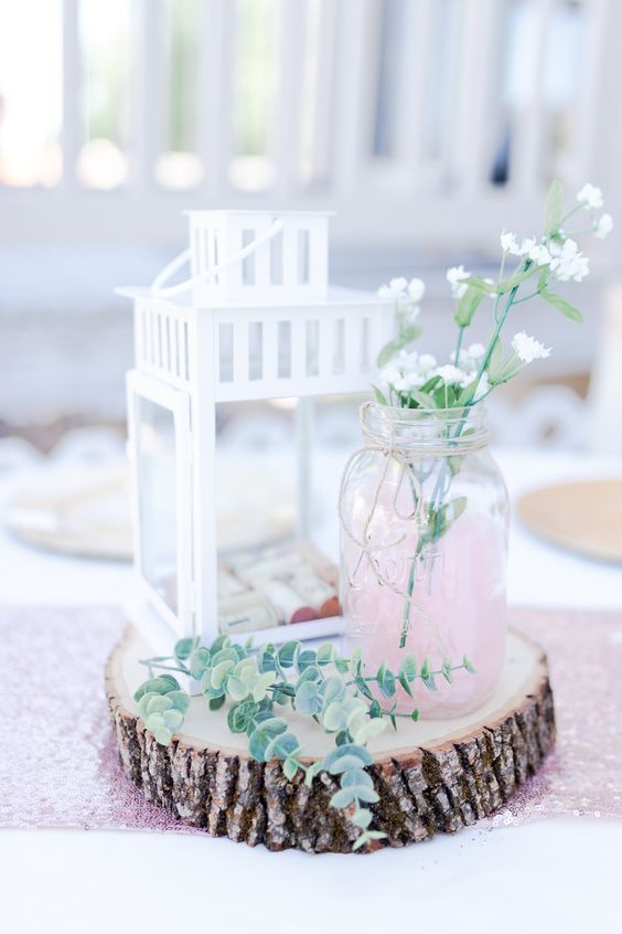 a wood slice, a white candle lantern with wine corks, a pink jar with some wildflowers and eucalyptus