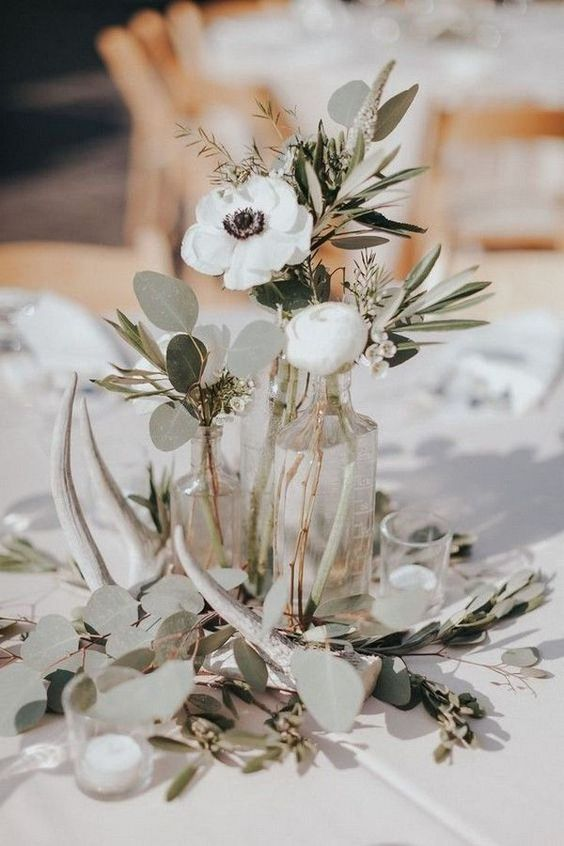 an elegant backyard wedding centerpiece of several bottles with greenery and white blooms, candles and antlers