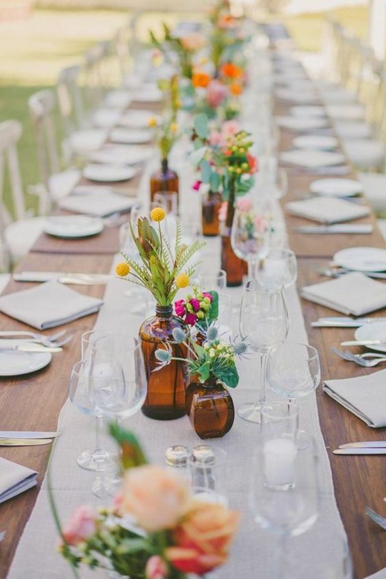 apothecary bottles and jars with colorful flowers and greenery and candles for decorating a backyard wedding table