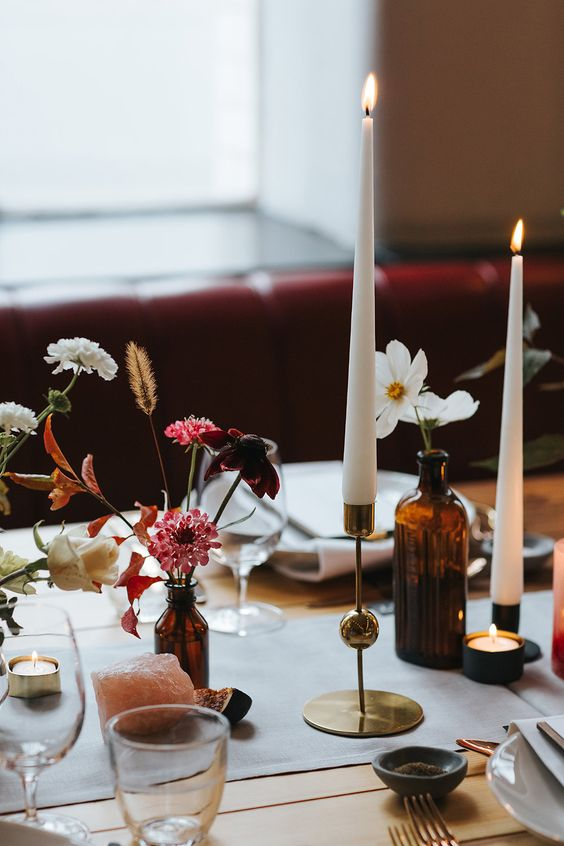 apothecary bottles with various flowers and dried elements, agates and tall candles for a refined wedding tablescape