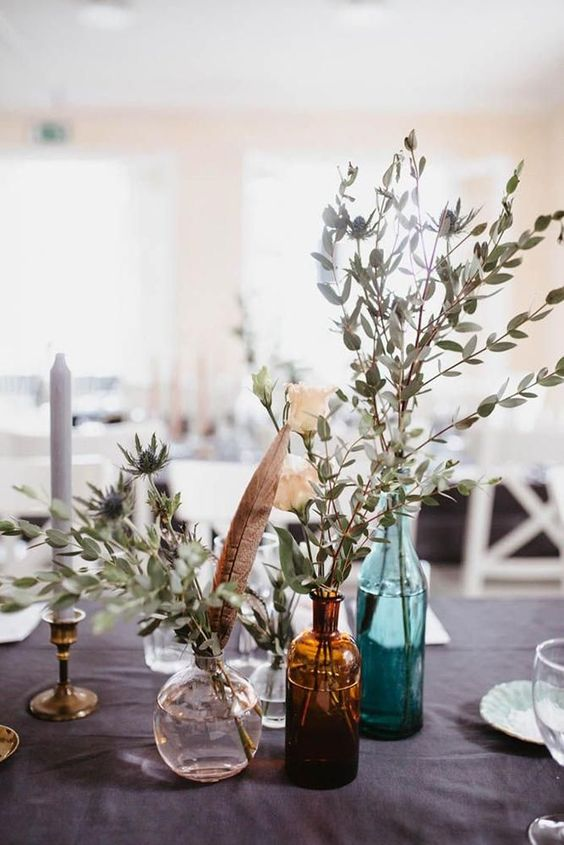 bottles with thistles and eucalyptus, candles and feathers for a boho backyard wedding centerpiece