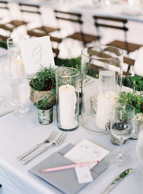 pillar candles in candle holders, greenery in vintage pots and mercury glass candle holders to rock