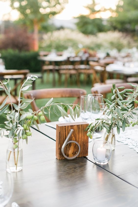 sheer bottles with olive branches and wooden table number will make up a cool table decor combo for a backyard wedding