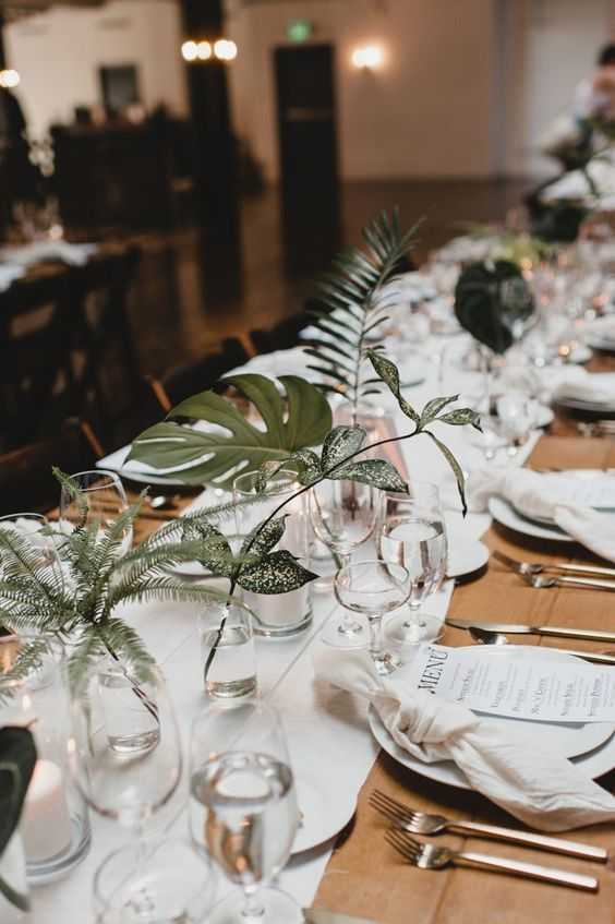 simple clear glasses and vases with statement foliage and greenery make the table look fresh and stylish