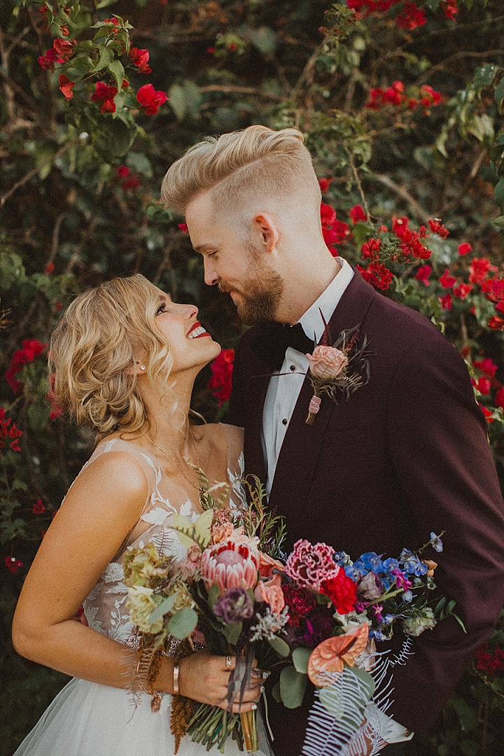 This couple went for a dramatic and moody fall wedding with lush and bright florals