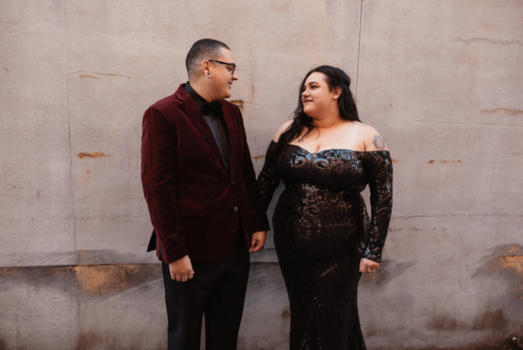 The bride was wearing a fitting off the shoulder embellished wedding dress and the groom was wearing black pants, a shirt and a burgundy velvet blazer