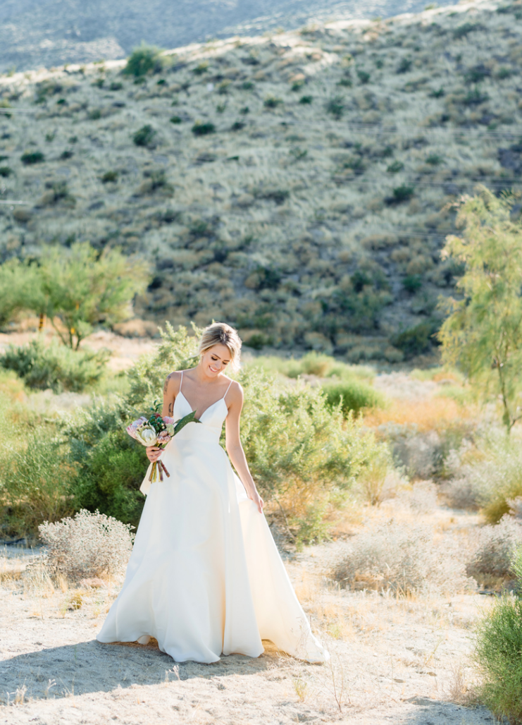 The bride was wearing a minimalist A-line wedding dress with a plunging neckline and rocking an updo