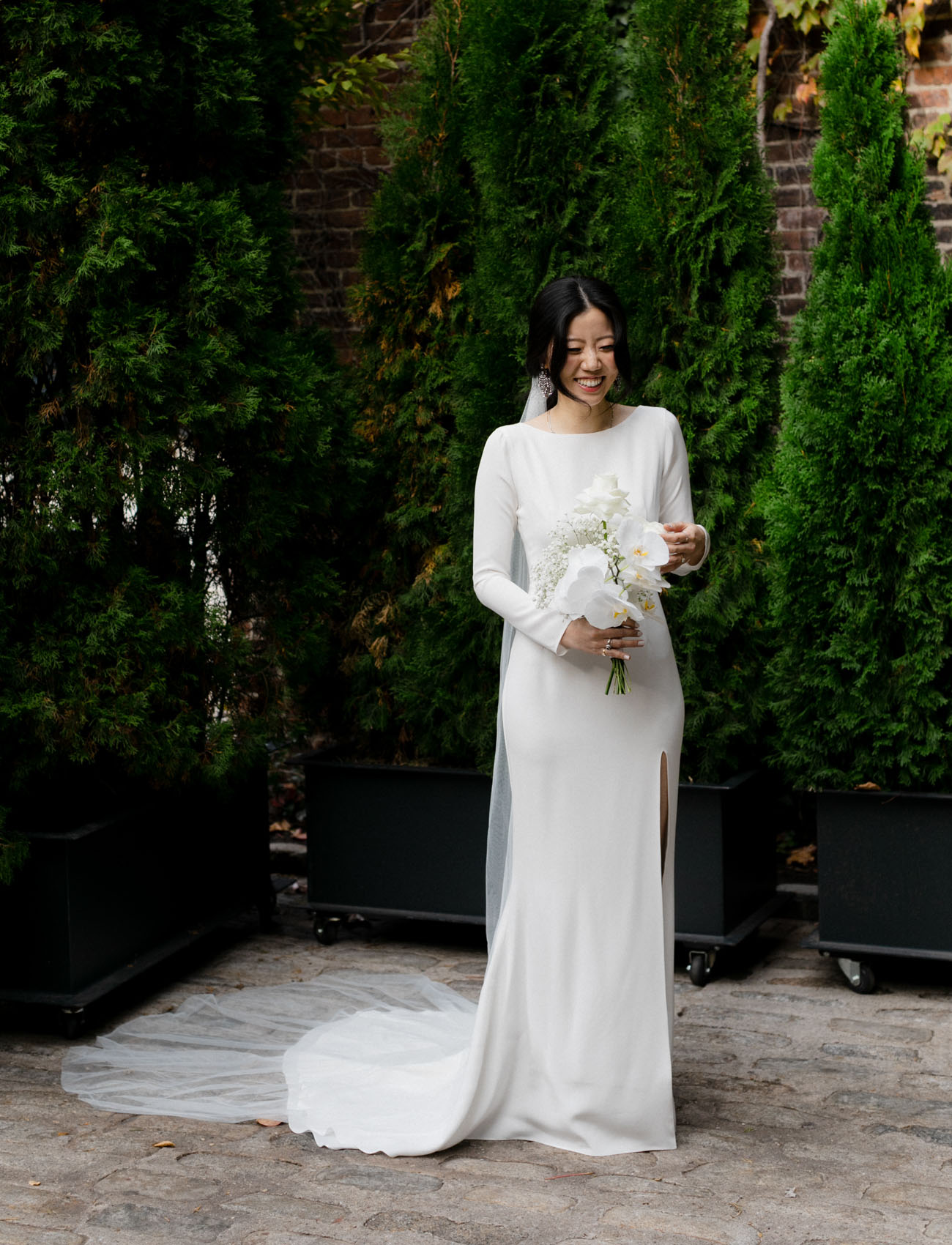 The bride was wearing a plain wedding dress with a high neckline, long sleeves and an open back plus a long veil